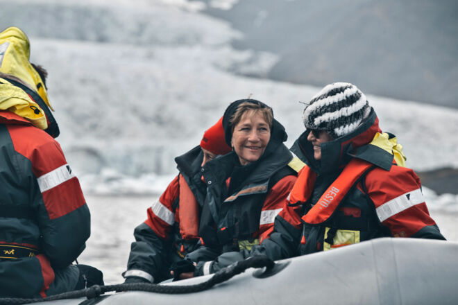 Man and a woman enjoying a boat tour on a glacier lagoon.