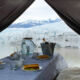 A dining table in a tent with a view to a glacier edge.